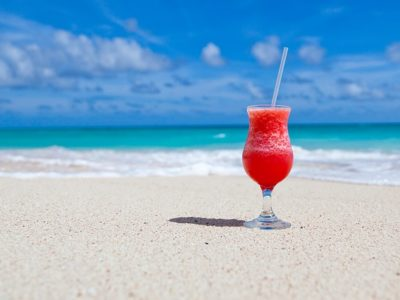 Cocktail de fruits rouges posé sur une plage de sable de la Côte d'Azur.