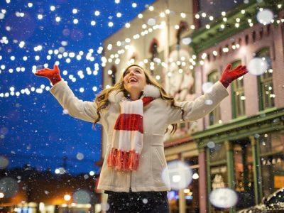 Une jeune femme s'extasie sous les décorations de Noël et la neige.