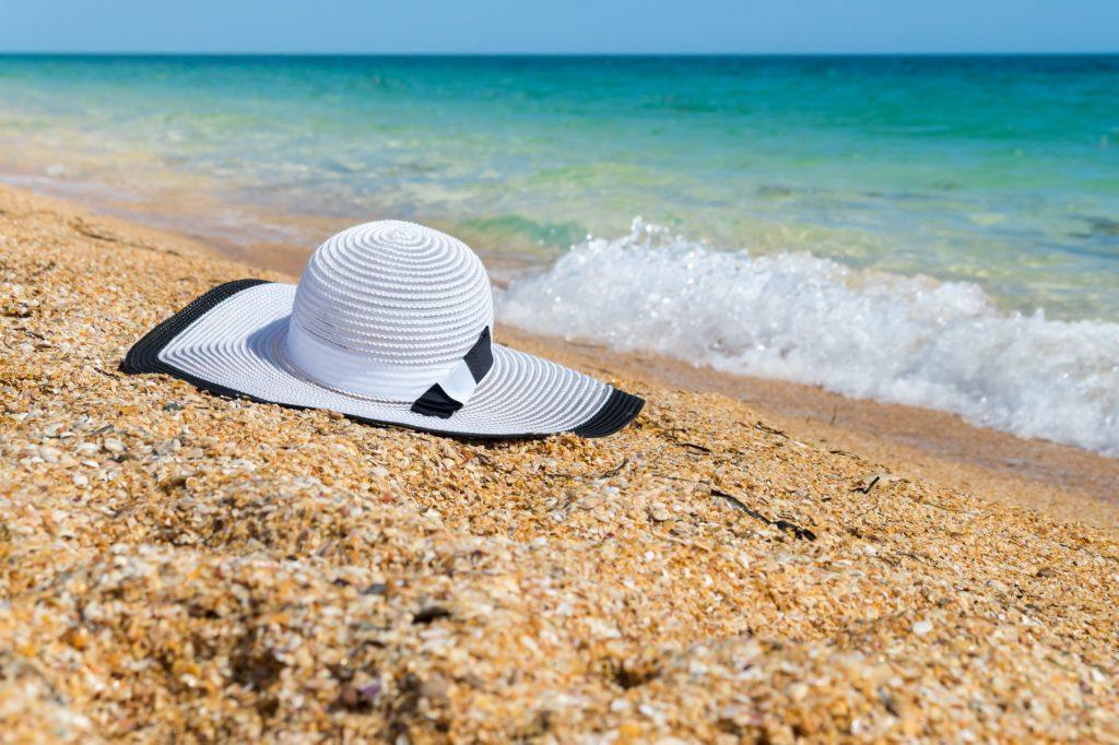 Chapeau blanc au bord de l'eau sur une plage de sable.