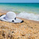 C'est une plage et au bord de l'eau de sable, il y a un chapeau blanc.
